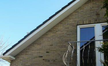 Huis met dakoverstek met windveer